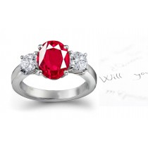 Three Stone Ruby Engagement Ring: Platinum ruby diamond ring set with center oval ruby and side diamond rounds.