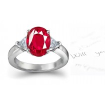 Classic Ruby Engagement Ring: Platinum ruby oval and diamond trillions three stone engagement ring.