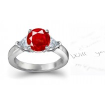 Royal Red Ruby Diamond Engagement Ring: Platinum three stone ruby ring set with a round ruby and two diamond pears.